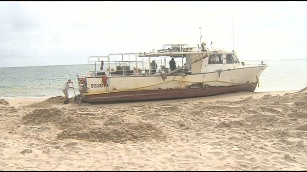 Fishing boat remains stuck on shore after running aground